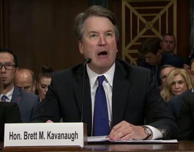 Judge Brett Kavanaugh, wearing a black suit, white shirt, and blue tie, is visibly angry as he responds before the Senate at his confirmation hearings to be a Supreme Court justice.