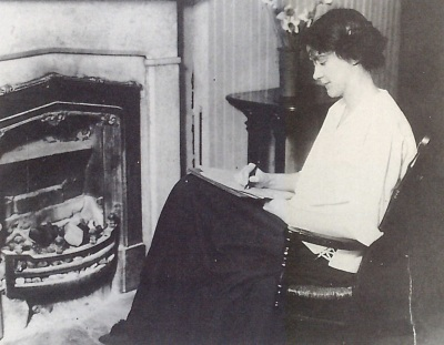 In a black and white photo, a woman, author Susan Glaspell, sits writing in front of a light colored fireplace. She is wearing a white shirt and dark skirt, and sitting in a rocking chair.