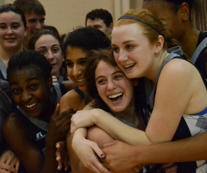 A group of young female basketballs hug after a win.