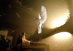 An angel appears, floating in the air above the bed of a man who is sitting up.
