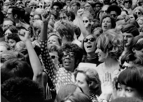 A black and white image of mass group of women with raised fists.