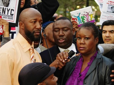 Two black men and a black woman speak into a microphone at a street protest.